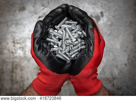 Person wearing protective gloves holding a handful of bolts and nuts in cupped hands against metal background