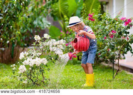 Child Gardening. Boy With Watering Can In Garden.