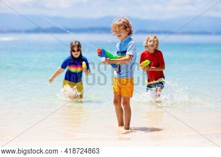 Child With Toy Water Gun. Kids Vacation Beach Fun.