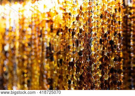Polished Amber Beads. A Wall Of Beads Under A Bright Light. Beautiful Natural Amber.