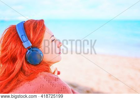 Redhead Girl With Closed Eyes Listening To Music With Headphones. Pretty Woman Listening To Music On