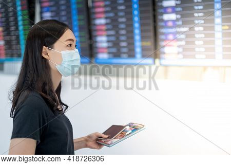 Asian Woman Wearing Surgical Mask And Holding Passport In Her Hand And Luggage Looking At The Flight