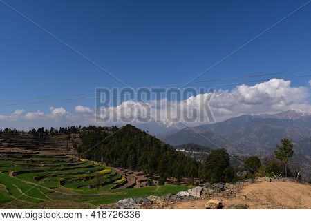 Beautiful Green Fields In Mountain Valley And Snow Caped Mountains