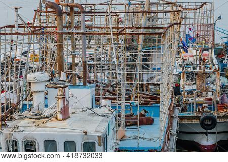 Equipment Cages On Top Of Ocean Fishing Trawlers Moored At Seaside Port.