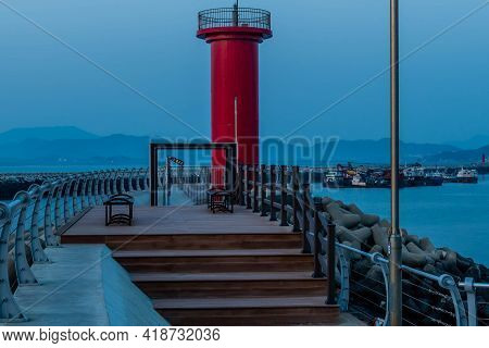 Red Lighthouse Behind Park Benches On Pier With Hazy Blue Sky In Background.