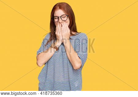 Young read head woman wearing casual clothes and glasses laughing and embarrassed giggle covering mouth with hands, gossip and scandal concept