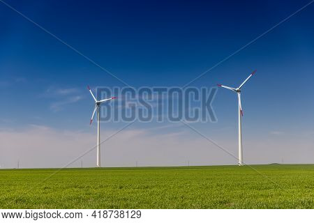 Windmills Stand On A Large Field. Alternative Energy Concept
