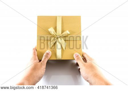 Hand Give Golden Gift Box With Golden Bow Isolated On White Background