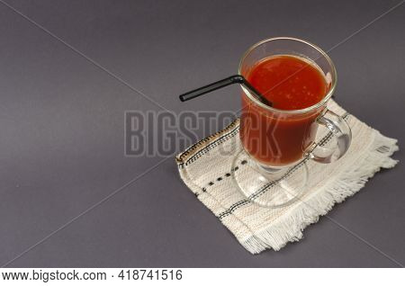 A Full Goblet Of Tomato Juice With Cocktail Straw On A Gray Background. The Glass Stands On Top Of A