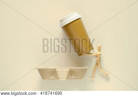 Wooden Model Holding Reuse Coffee Tumbler To Put On Recycle Paper Tray. World Environment Day Concep