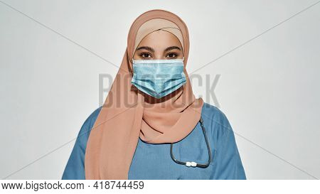 Portrait Of Young Arabian Girl Doctor In Protective Mask Looking At Camera While Posing On Light Bac