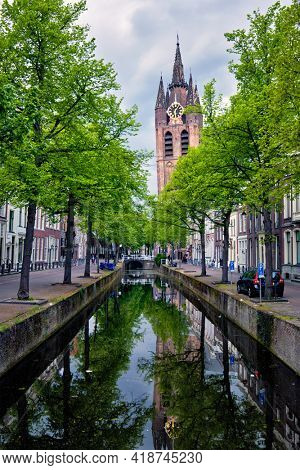 Delt canal with old houses bicycles and cars parked along and Oude Kerk Old church tower. Delft, Netherlands