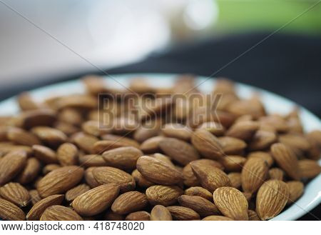 Dried Brown Toasted Almonds Nut Inside White Plate, Vegetarian Meal, Healthy Eating Ready For Eat