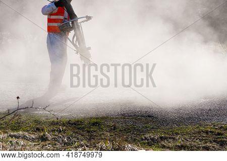 Spring Fast Repair Of An Asphalt Road. Worker In Uniform During Fast Repair Road Surface. Granite Cr
