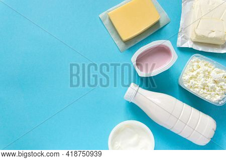 Flat Lay Of Dairy Products. Milk, Curd, Sour Cream, Cheese And Butter On Blue Background, Copyspace