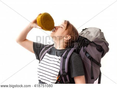 A Girl In A Gray T-shirt With A Large Hiking Backpack Drinks From A Flask On A White Background. The