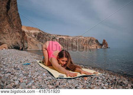 Young Woman In Pink Swimsuit With Long Hair Practicing Stretching Outdoors On Yoga Mat By The Sea On