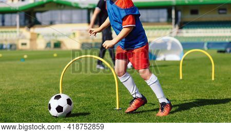 Child Playing Soccer Ball On Practice Unit. School Physical Education Class For Kids. Football Sport