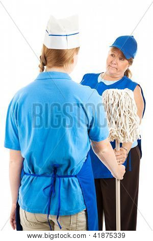 Teenage worker getting handed the mop by her store manager.  Isolated on white.