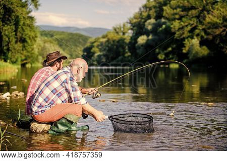 Sharing His Secrets. Transferring Knowledge. Friends Spend Nice Time Riverside. Experienced Fisherma