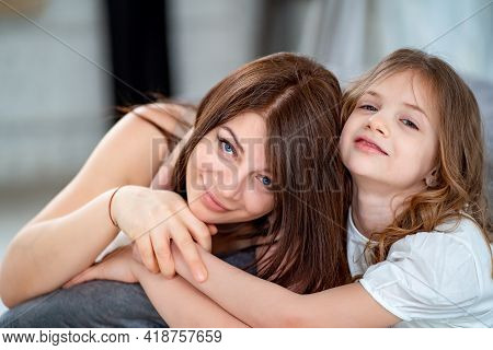 Mom Cuddles With Her Daughter. Happy Family.