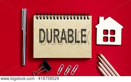 Durable Text Written On Notebook With Pencils And Office Tools And Model Wooden House