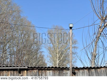 Wooden Support With Diode Soffit And Wires. Rural Landscape. Homemade Lighting Pole With Stretched W