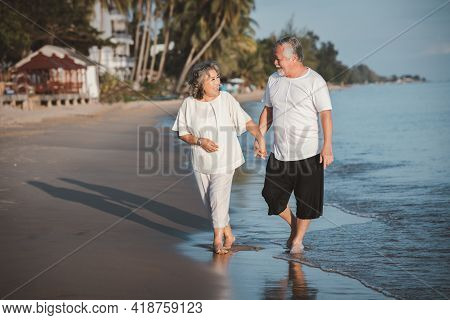 The Romantic Asian Senior Couple Hugging While Standing On Summer Beach Sunset. Travel Leisure And A