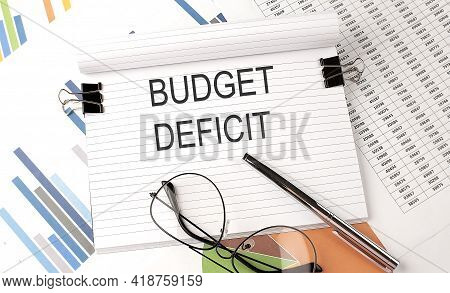 Notebook With Text Budget Deficit On The Table With Charts,pen And Glasses.