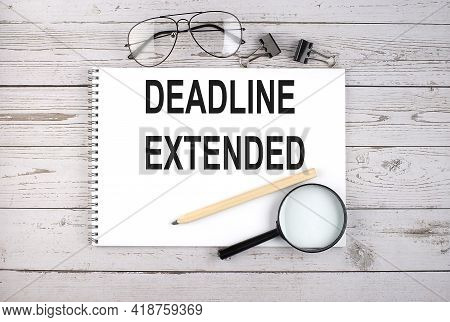 Notebook With Text Deadline Extended On The Wooden Table With Pen, Magnifier And Glasses