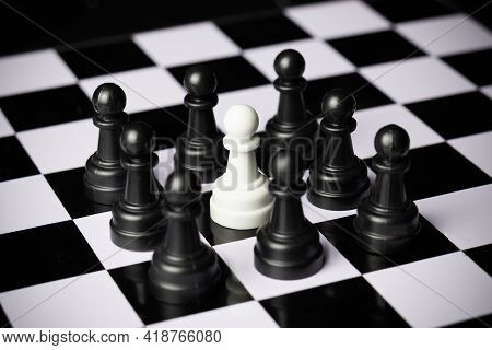 Black Pawns Surrounding A White Pawn On A Chessboard.