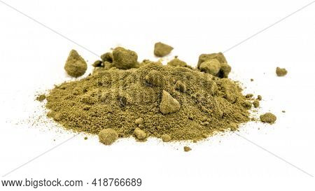 wheatgrass powder heap on a white plate, alkalizing green superfood containing fiber, chlorophyll, phytonutrients, amino acids, antioxidants, selenium, iron and vitamins.