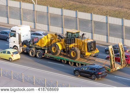 Truck With A Long Trailer Platform For Transporting Heavy Machinery, Loaded Tractor With A Bucket. H