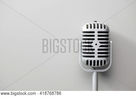 Metal retro microphone. Vintage microphone on gray background. Top view.