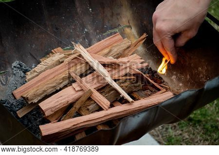 Starting The Campfire In A Firepit With Kindling And Safety Matches. Camping Lifestyle