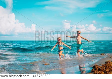 Little Girl And Boy Run And Play With Water At Beach