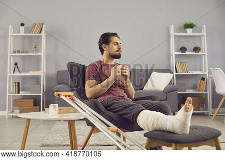Man With Broken Leg Sitting In Armchair, Thinking About His Injury And Feeling Bored And Lonely