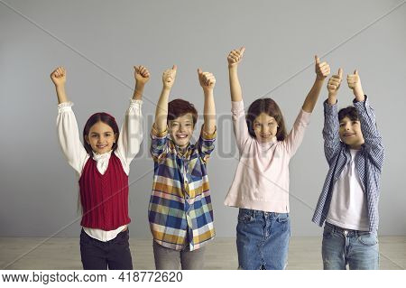 Energetic Optimistic Preteen Children Show Hand Up With Thumbs Up Gesture