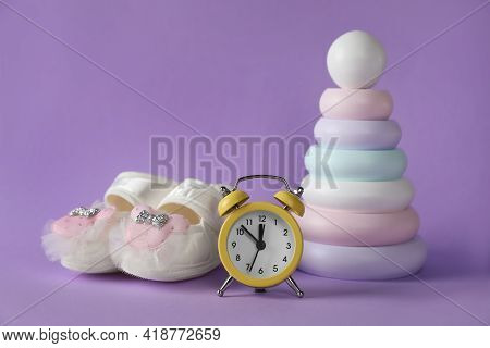 Alarm Clock, Toy Pyramid And Baby Booties On Violet Background. Time To Give Birth
