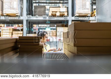 Asian Female Worker In Safety Vest Sitting And Working With Computer Laptop In Storage Warehouse. Pe