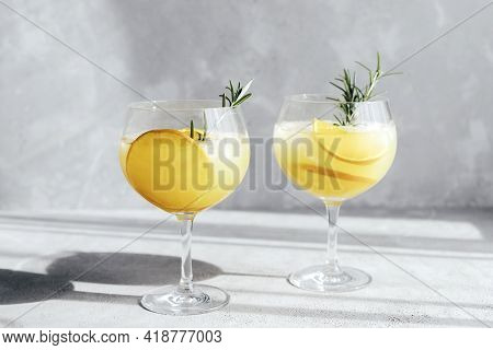 Glasses, Glasses With A Summer Refreshing Cocktail With Orange And Ice Cubes And A Sprig Of Rosemary