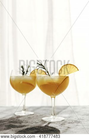 Glasses With Summer Refreshing Cool Drinks Or Cocktails With Orange And Rosemary Branch On The Table