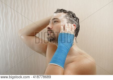 Broken Wrist In Modern Blue Waterproof Bandage. Handsome Middle-aged Man Takes A Shower With His Han