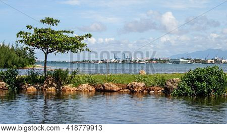 Calm Sea With A Natural Breakwater And Harbour In The Background In Puerto Rico