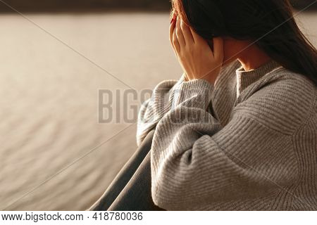 Side View Of Frustrated Young Female In Warm Knitted Sweater Covering Face With Hands And Crying Whi