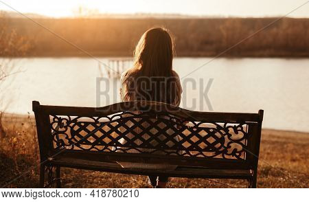 Back View Of Unrecognizable Female Sitting On Bench Near Lake And Contemplating Autumn Nature At Sun