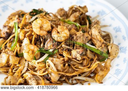 Close-up On Penang Char Kuey Teow Is Popular Fried Noodle With Coceral, Shrimp And Eggs In Black Sau