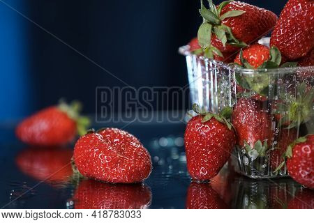 Big Red Strawberries In A Plastic Box Closeup In A Dark Blue Background. Healthy Lifestyle. Multivit