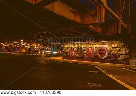 NORWALK, CT, USA - APRIL 24, 2021: SONO sign under railroad bridge on Washington Street  with evening lights