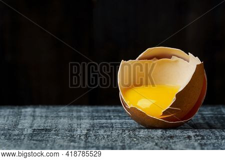 Broken Chicken Egg On A Black Wood Background With Copy Space. Whole Egg Yolk And Broken Eggshell. B